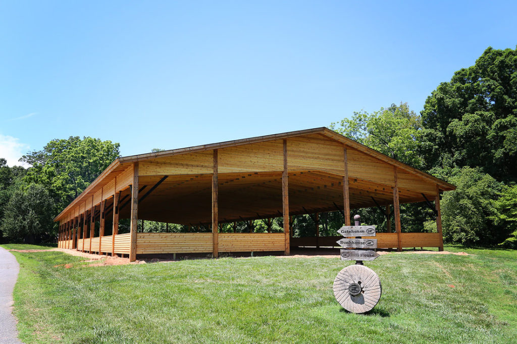 Wooden Pole Barn Riding Arena With Exposed Scissor Trusses
